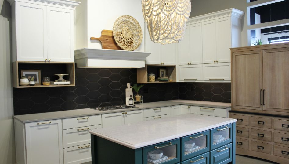 Image of kitchen with white cabinets, black backsplash and teal island