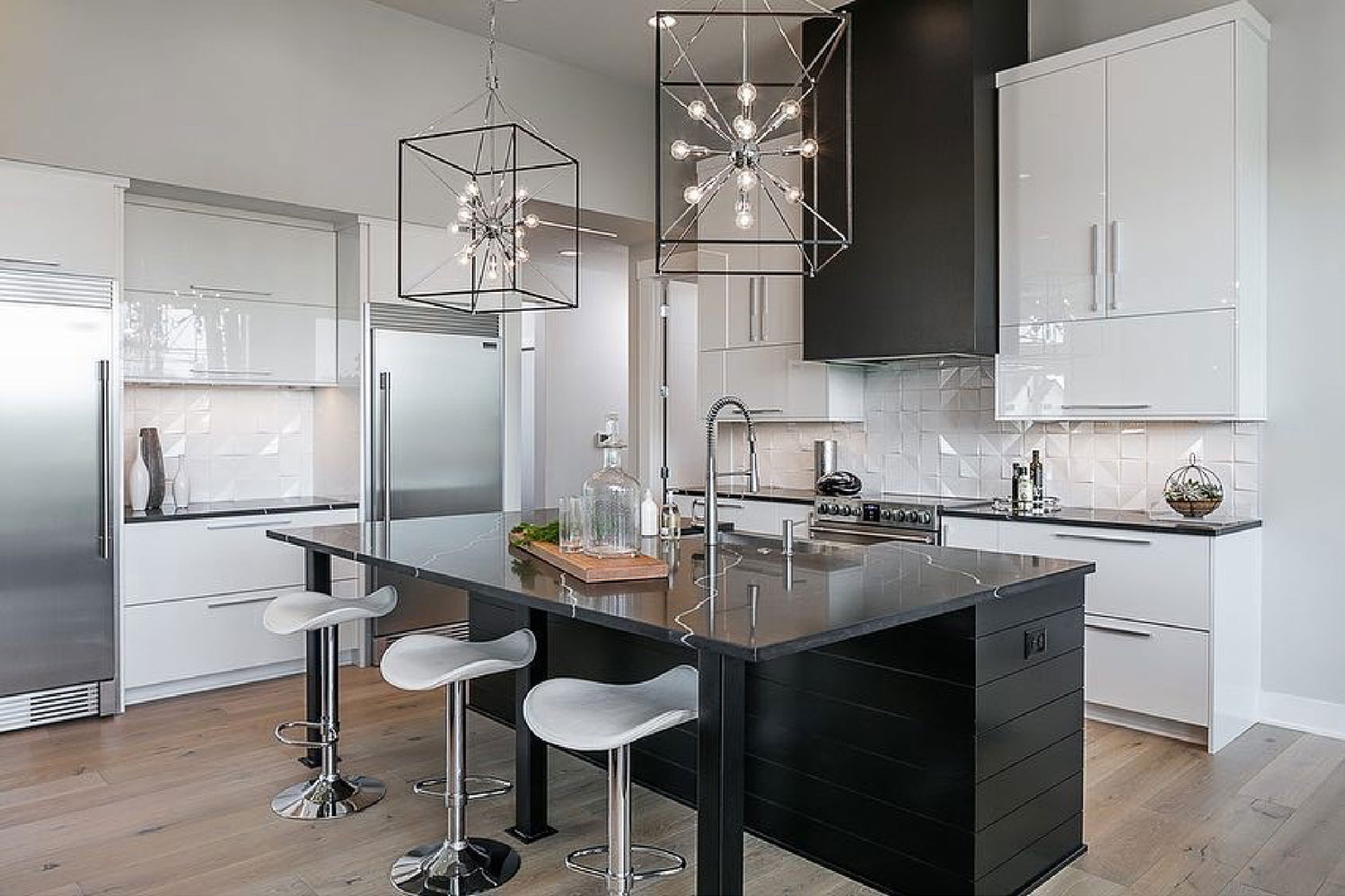 Image of kitchen with black island and countertops, and white cabinets with backsplash